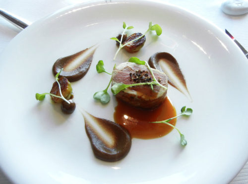 Lamb Saddle cooked in crepine perfumed with marjolaine flower, cauliflower puree and black garlic, green lentil gnocchi